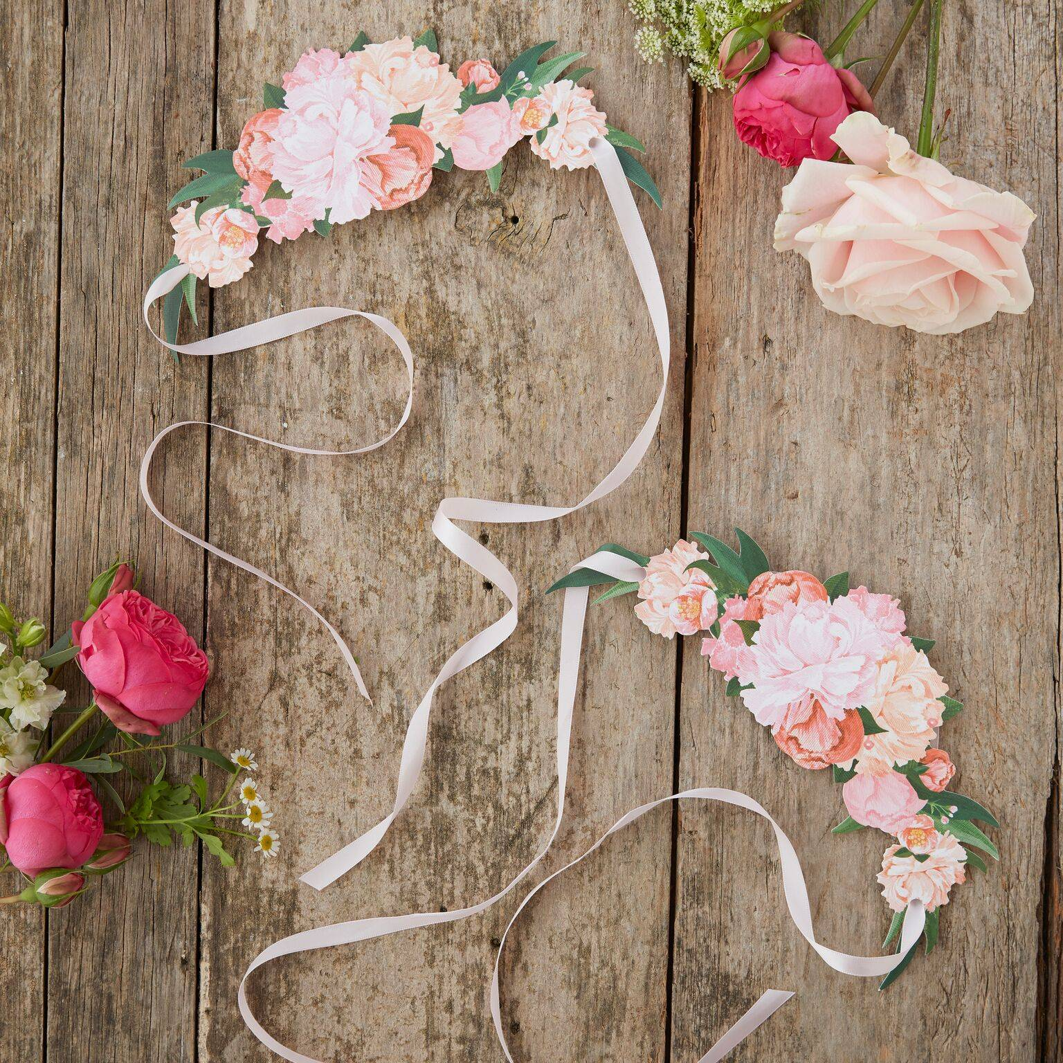 A top-down photo of a rustic wedding table with floral headbands and flowers laid out in pink hues