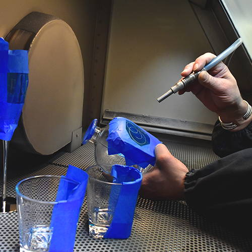 An engraver engraving glassware.