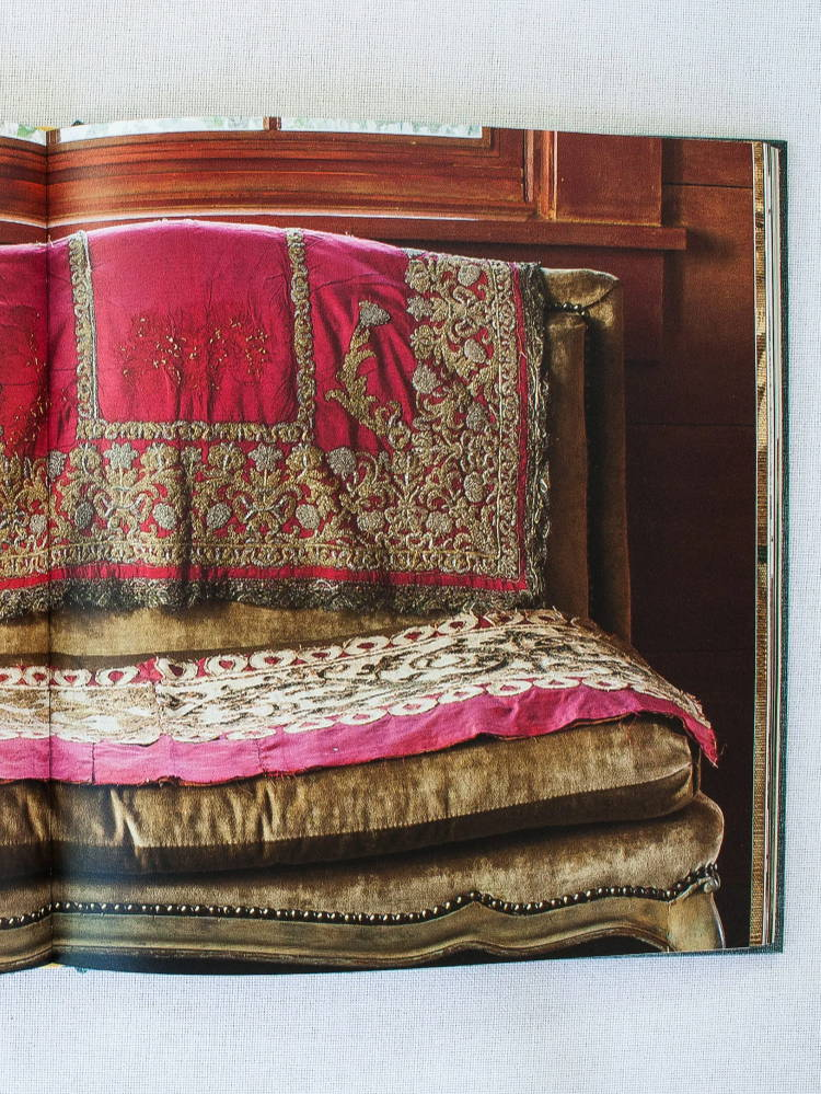 18th century gold and silver European embroidery on 19th century red silk cover hangs over a settee, pictured in Once Upon A Pillow