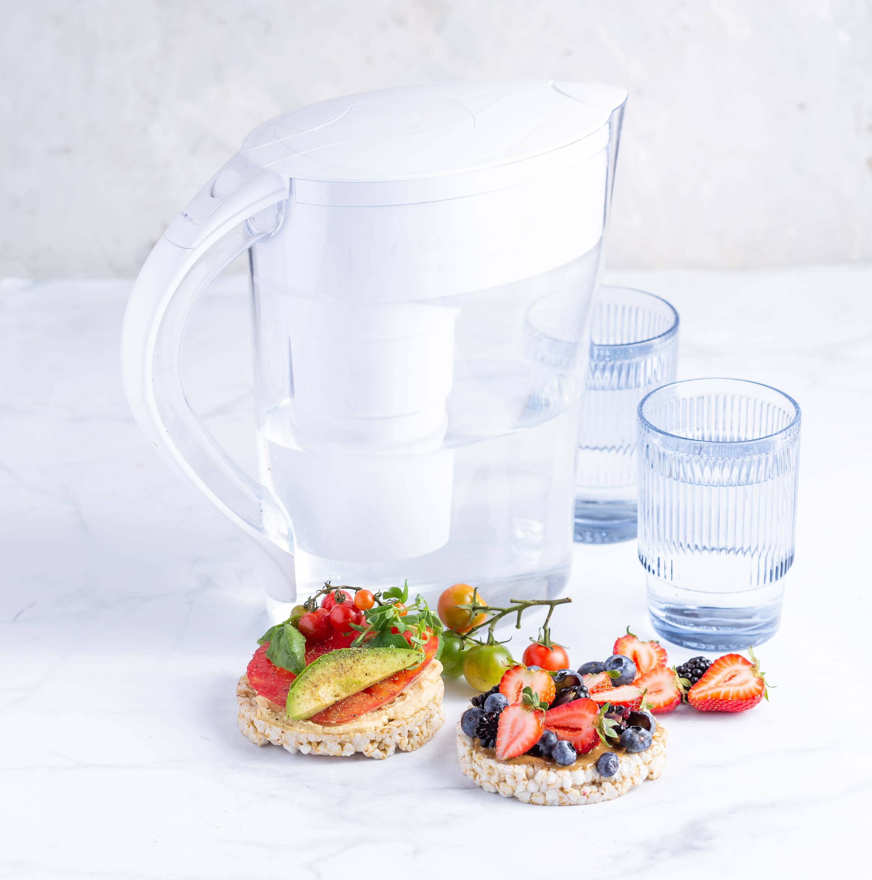 Water pitcher with glasses and food in front