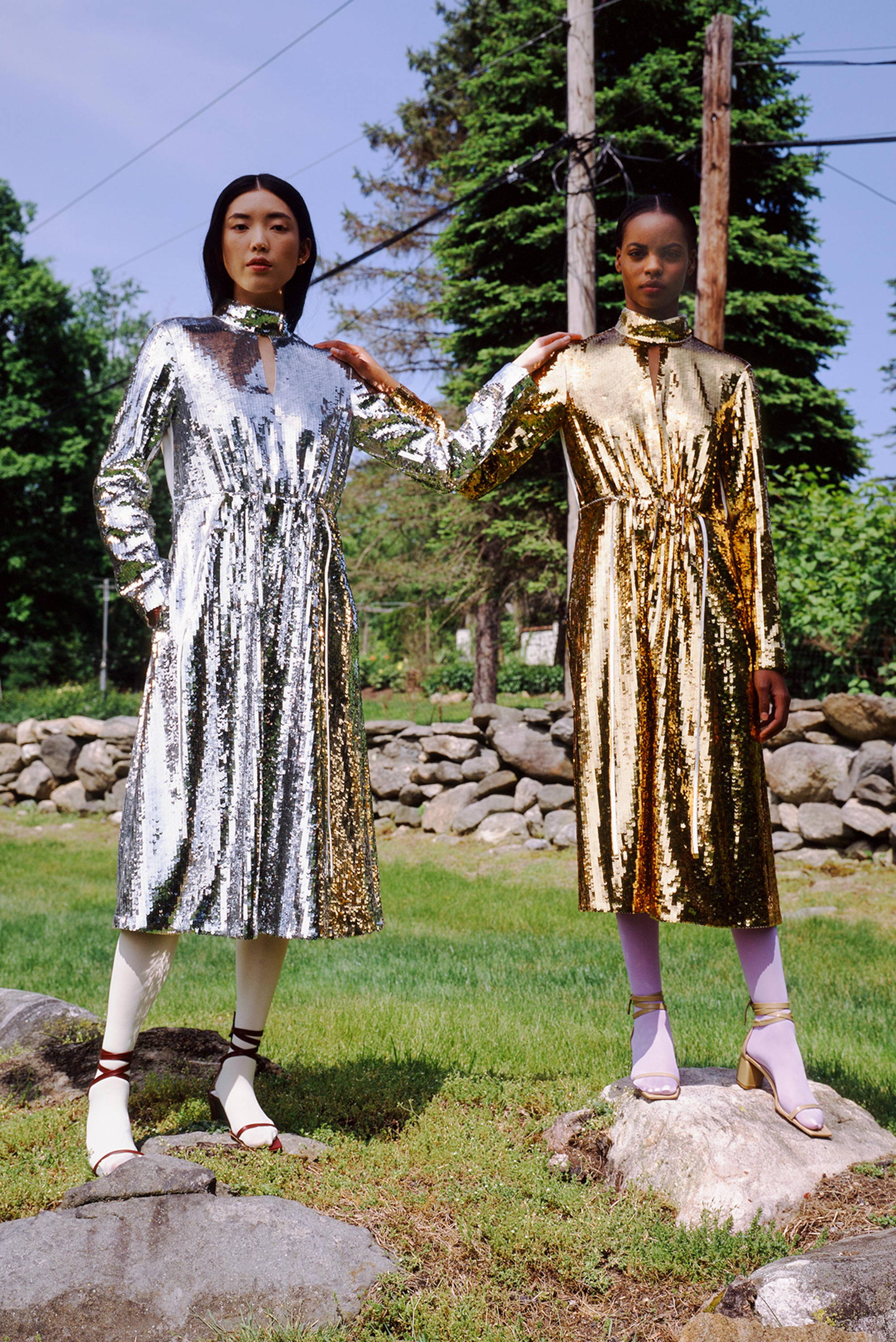 Two models wearing sequin dresses while standing on rocks.