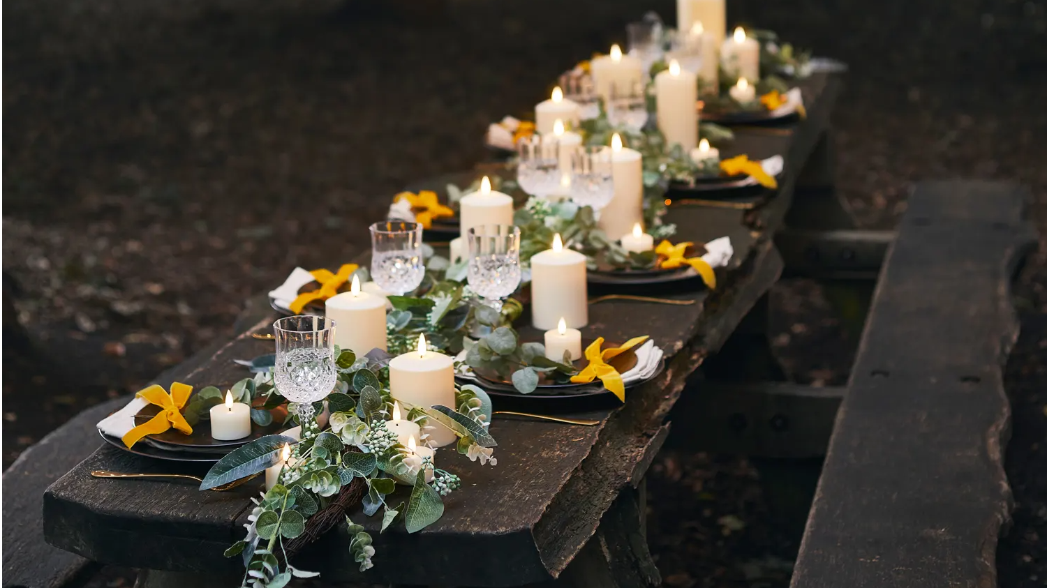 Wedding table with assortment of TruGlow candles and garland styled as part of centrepiece