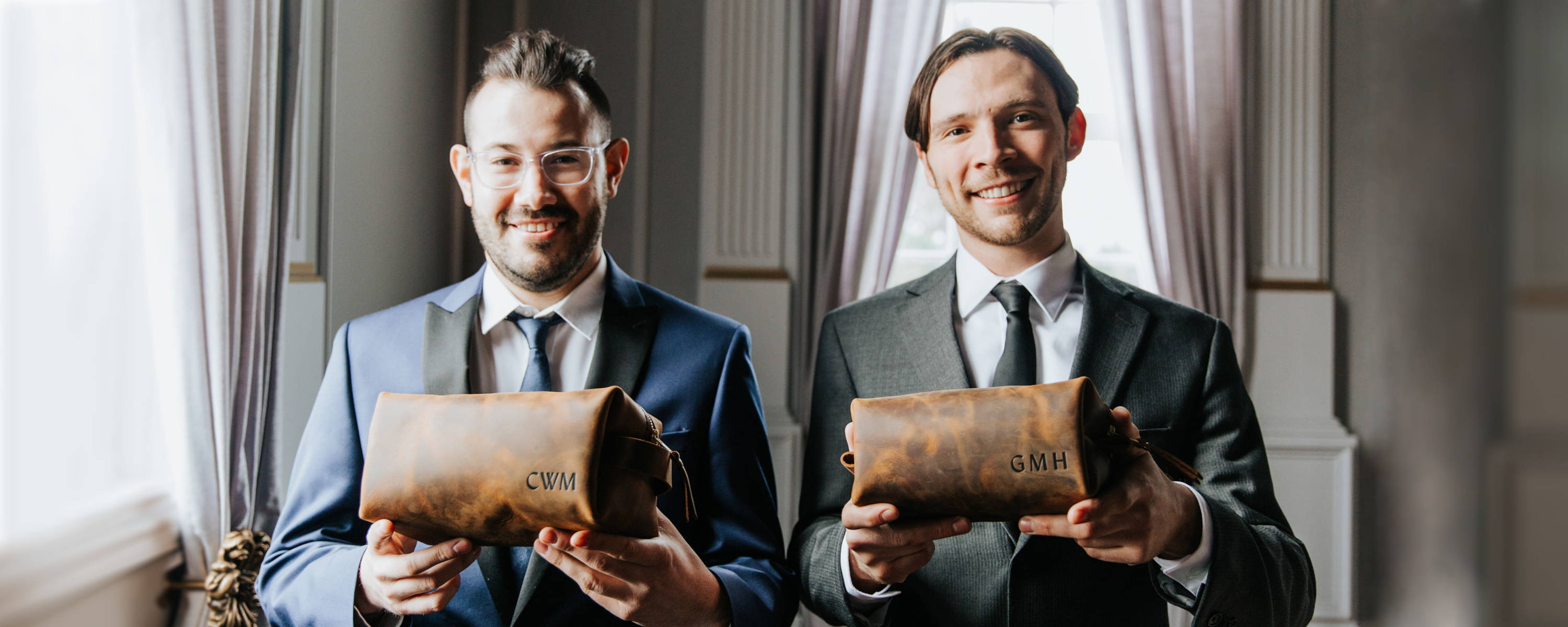 a groom and groomsman holding personalized handmade leather dopp kits made by portland leather goods