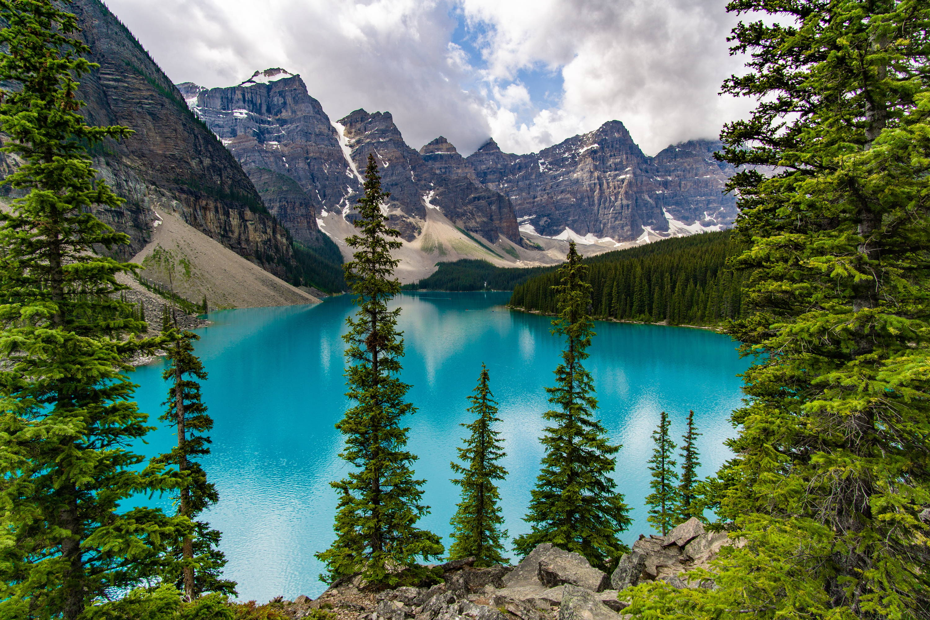 Things to Do in Banff: Blue glacier lake surrounded by evergreen trees to the right and foreground with stark mountains in the background.