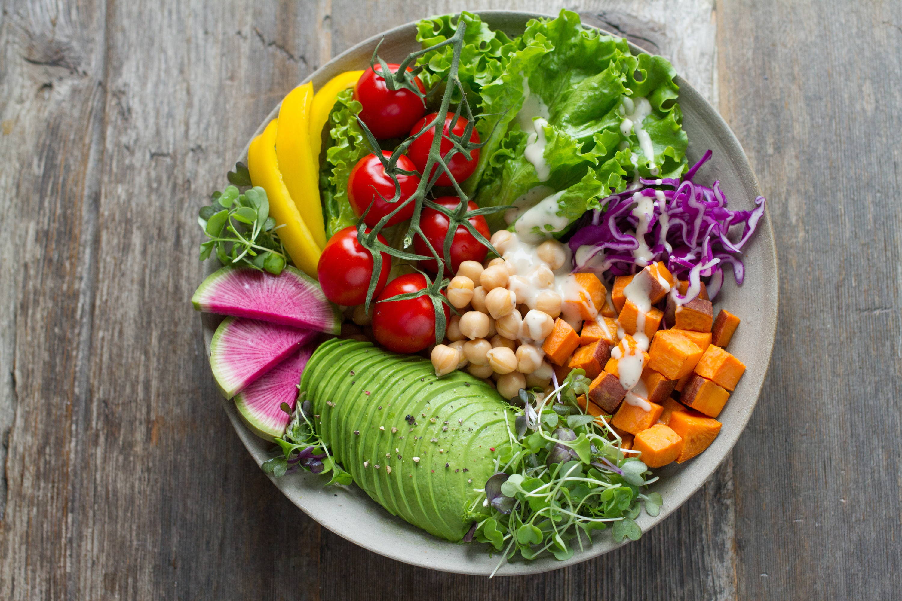 plant based salad plate with avocado lettuce tomatoes radishes yellow pepper cabbage, sweet potatoes and garbanzo beans