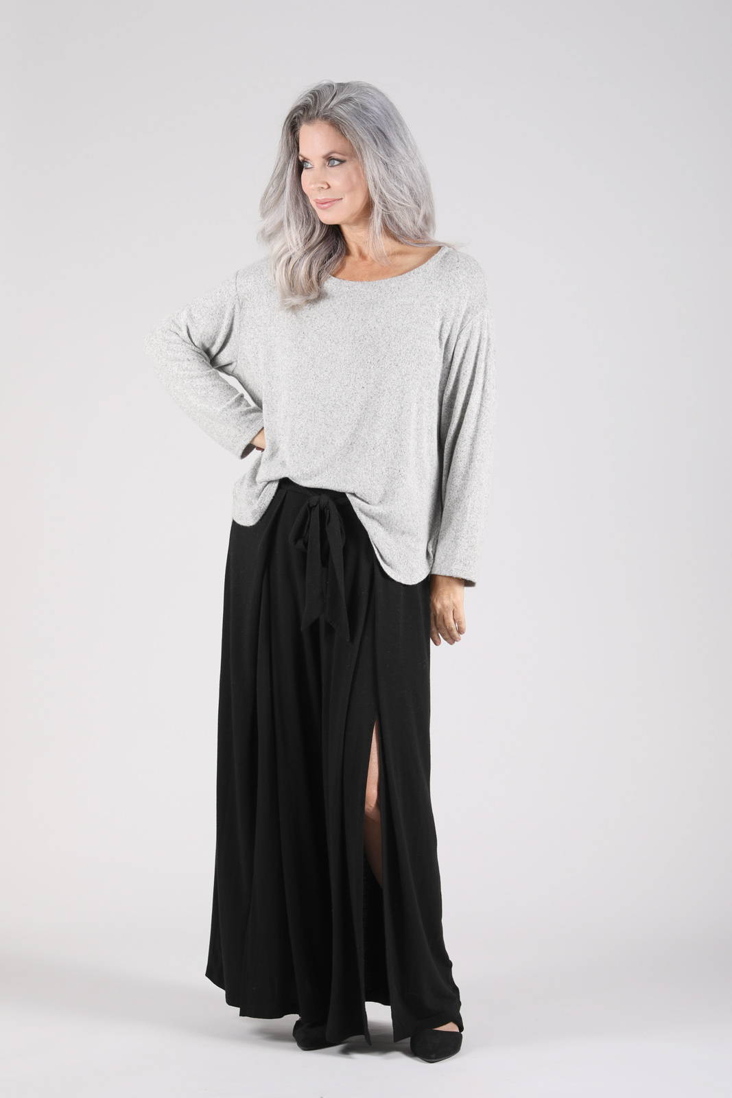 Model wearing the Valo Sweater with heather grey with the Grian Pant in black
