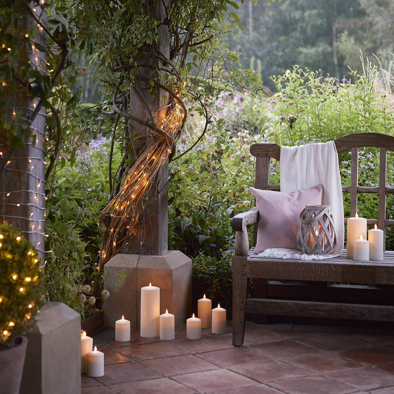 lifestyle avec bougies extérieures TruGlow et lanterne en bois tresse sur banc et sur le sol.