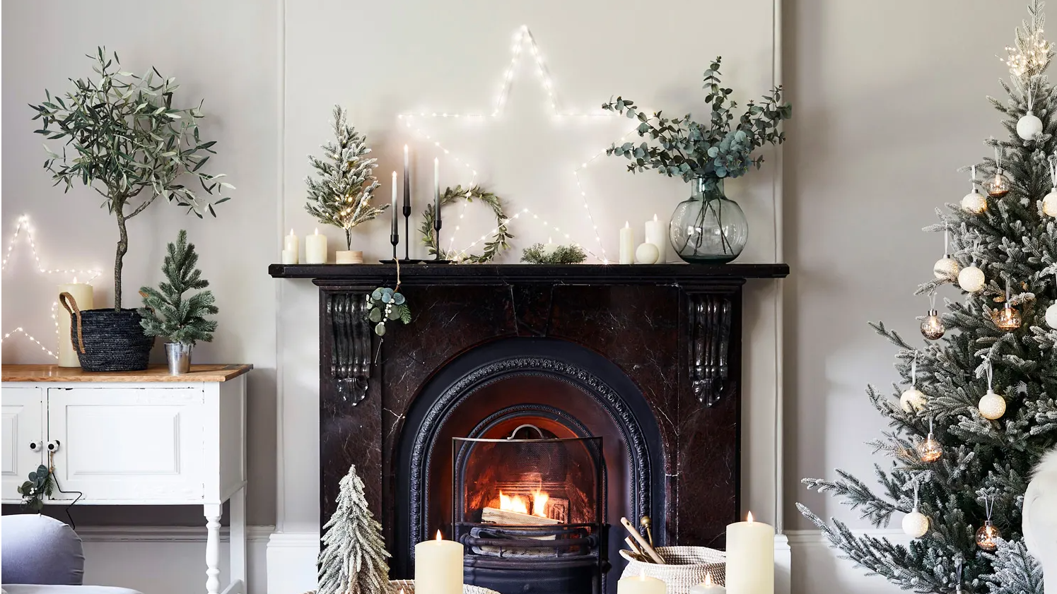 Festive fireplace in living room with oversized Osby star light illuminated on mantel with variety of festive foliage and mini trees with an assortment of TruGlow candles displayed