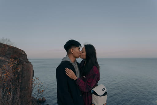Francis and Carol kissing with ocean in background