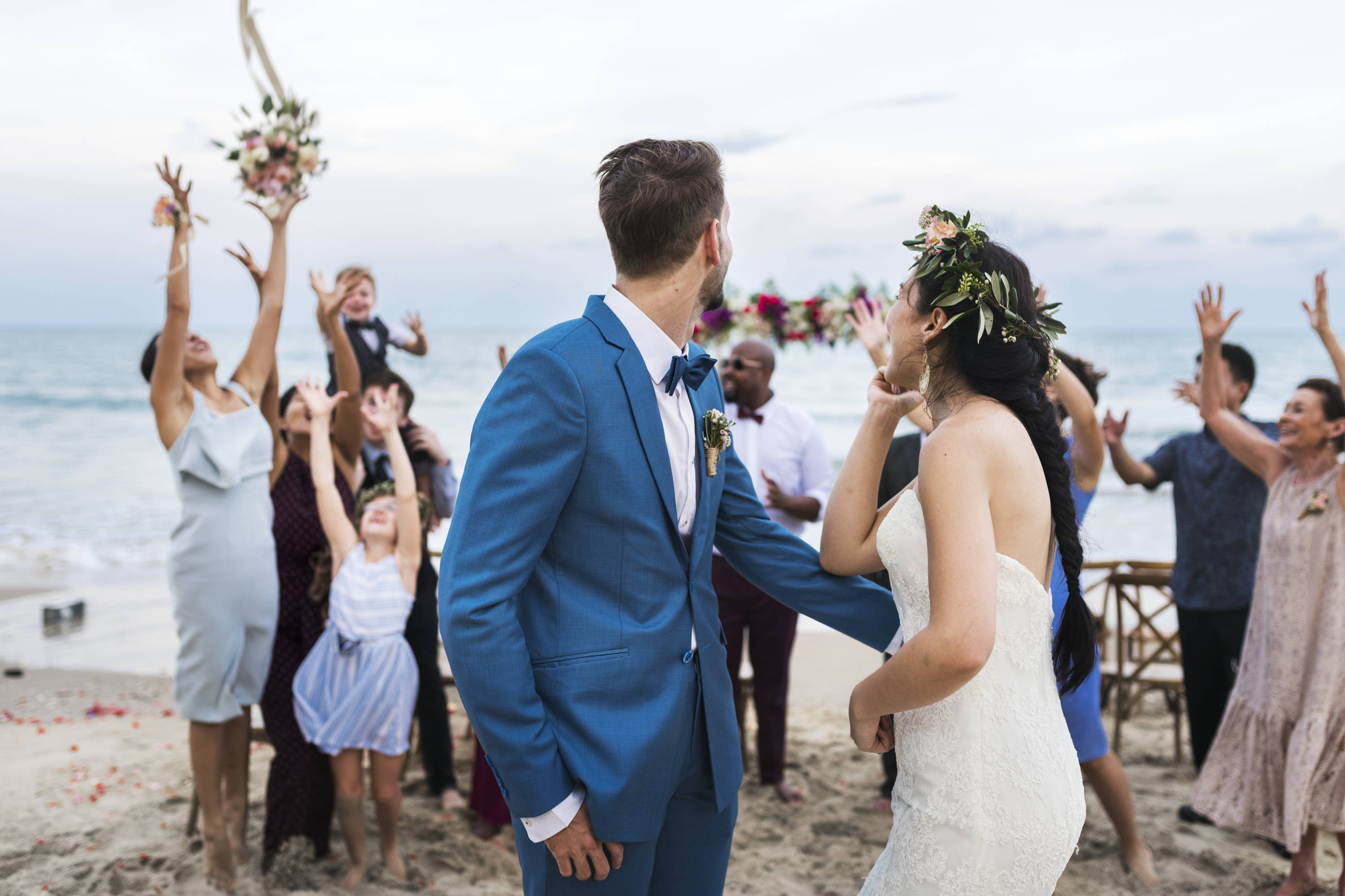 Wedding couple on beach throwing floral bouquet