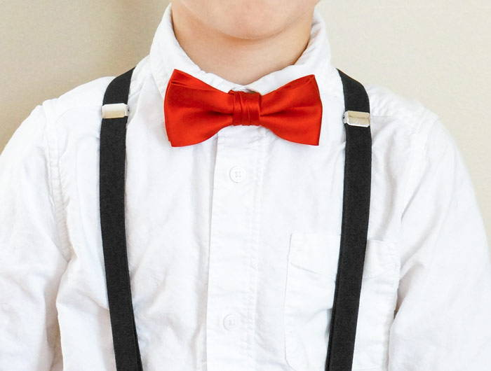 Boy wearing a red solid bow tie and black suspenders