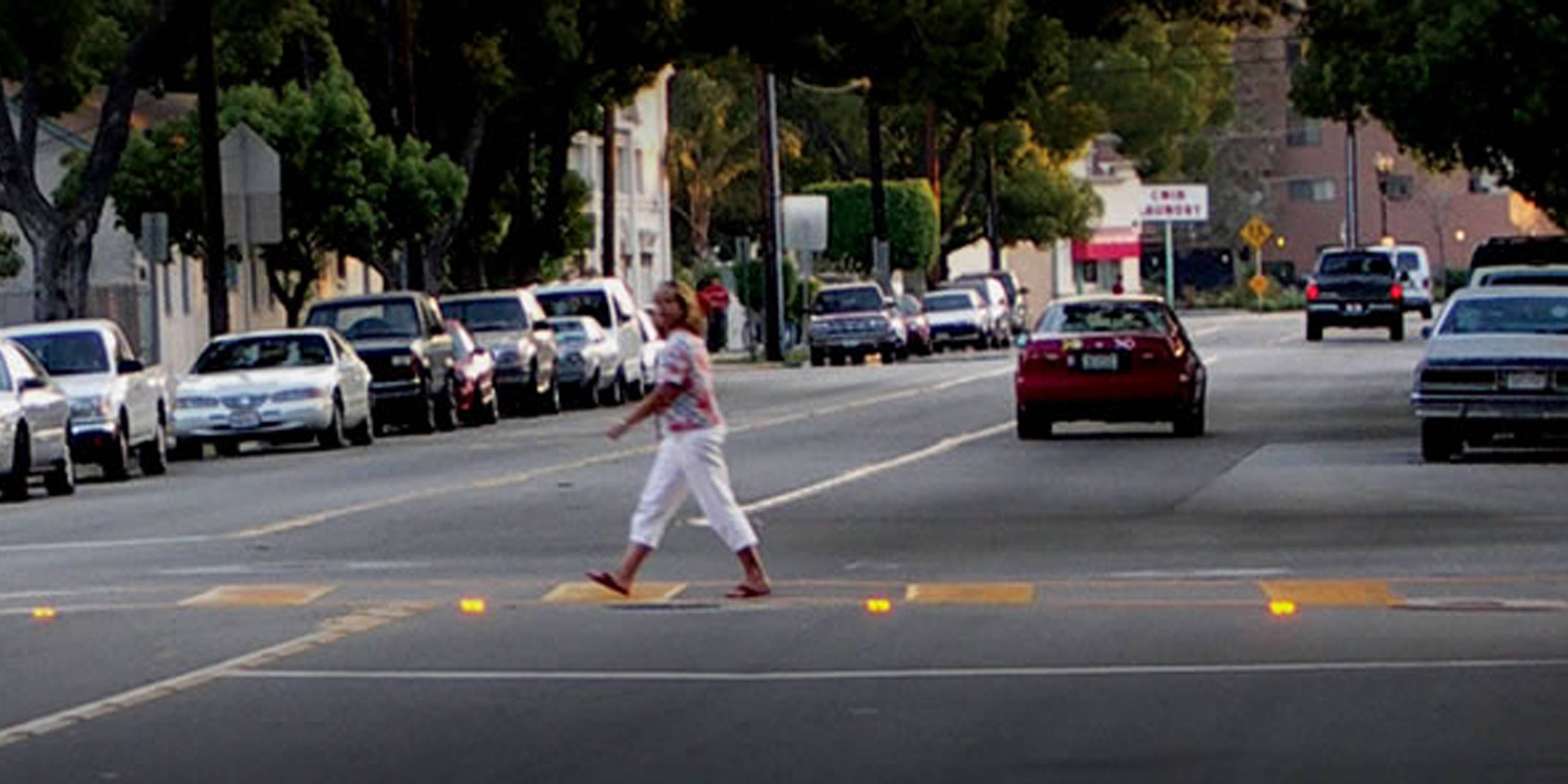 Woman crossing street with warning lights