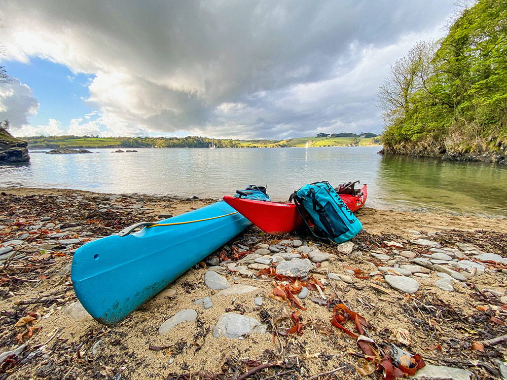 sea kayaks and the Solo SUP Backcountry inflatable paddleboard on a beach in England