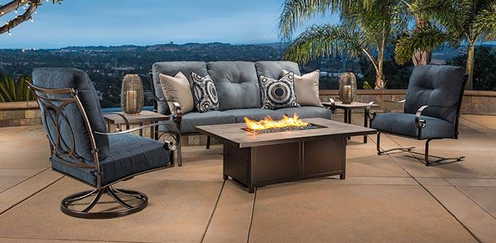 A full o.w. lee patio furniture and fire table set is on display in front of a cityscape at dusk.