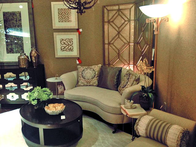 small round dark coffee table in front of brown fabric settee