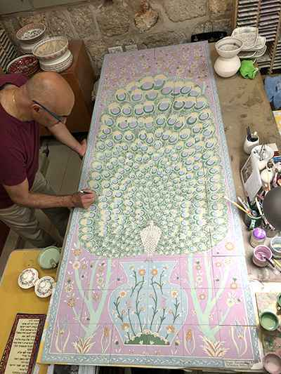 Hagop hand painting a custom tile mural for a residence in Miami, Florida