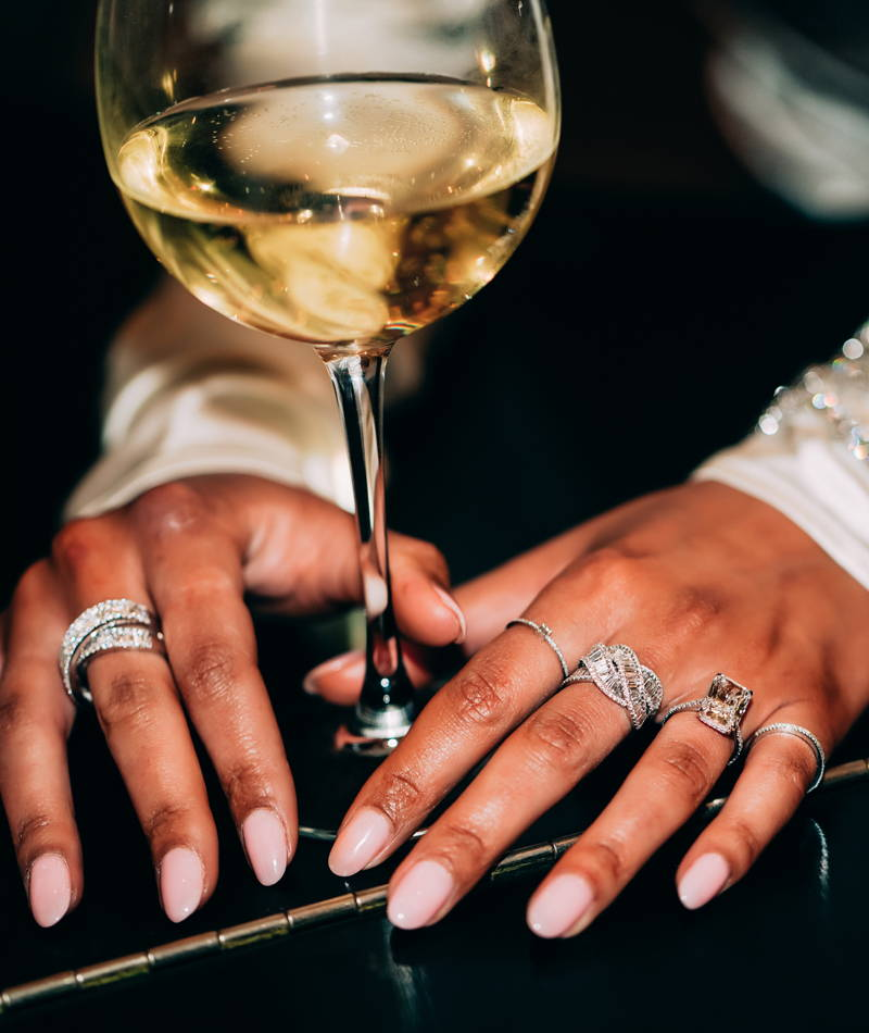 Model wearing Ring Concierge rings holding wine glass