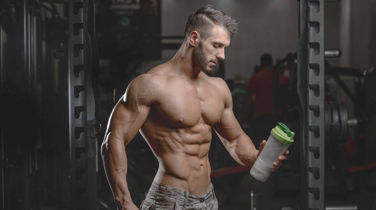 Handsome athletic fitness man holding a shaker and posing gym | The Essential and Optimal Drink for Bodybuilders | bodybuilding drinks | water for bodybuilders | Featured