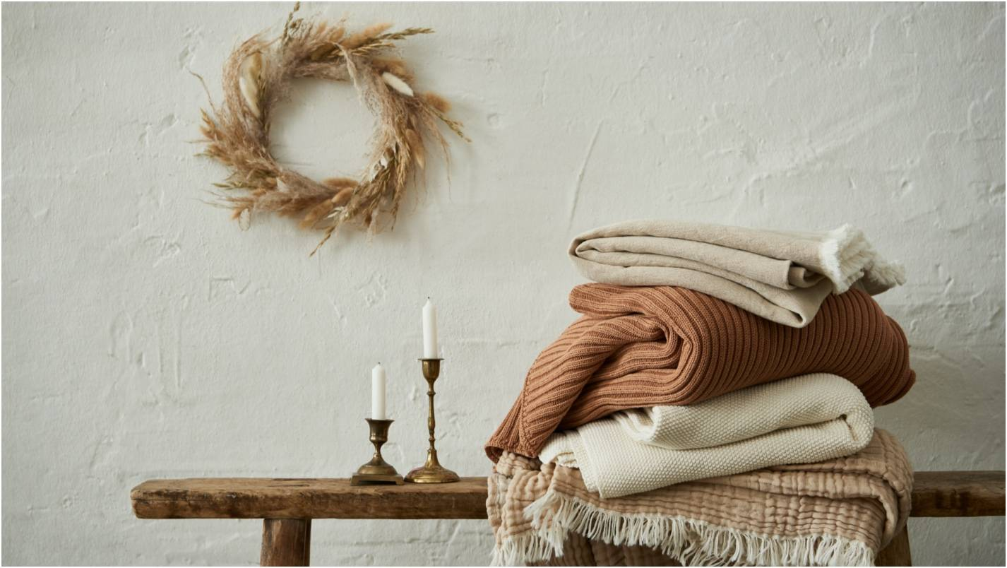 Pile of warm coloured blankets against a cream background.  Earthy tones.