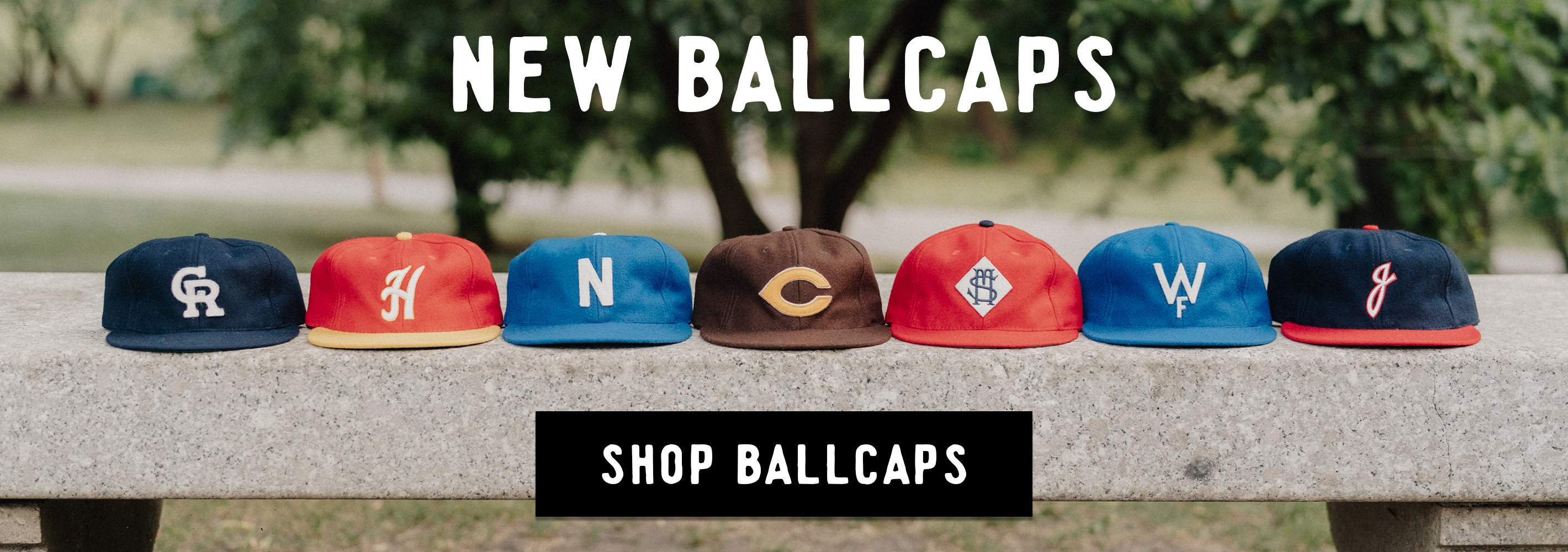 Photo of ballcaps on top of a bench.