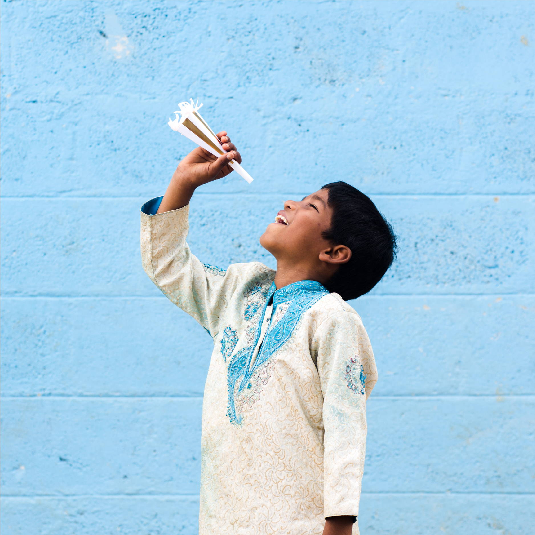 An Indian boy wearing traditional Indian clothing poses with a party horn in front of a blue wall with the look of pure joy
