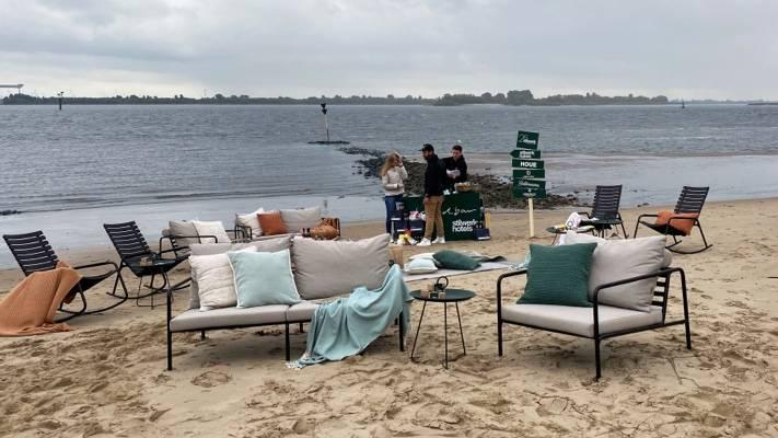 Bänke und Stühle mit gemütlichen Kissen und Decken am Strand
