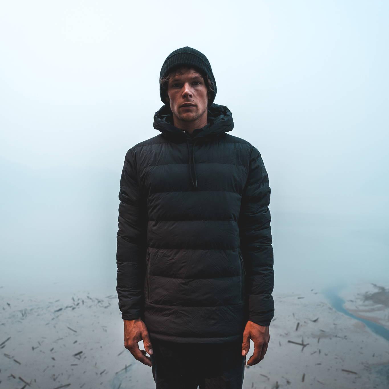 Man standing infront of ocean wearing Robson Down Hoody