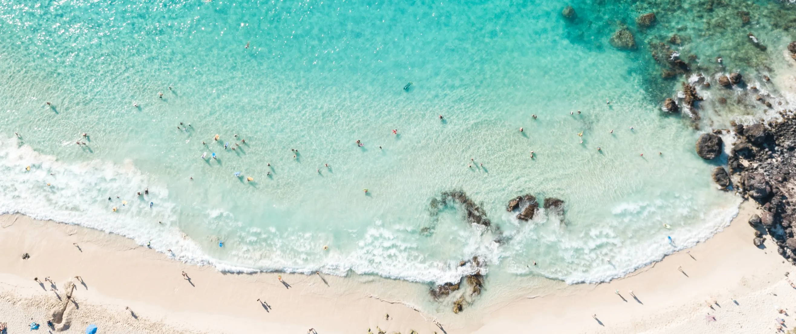 Aerial view of sandy beach and blue ocean with surfers in water