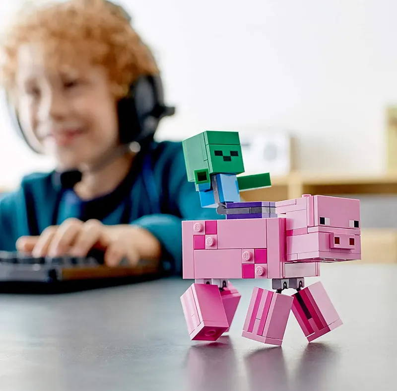 Image showing a kid playing a video game with the LEGO Minecraft Pig BigFig with Baby Zombie in the foreground