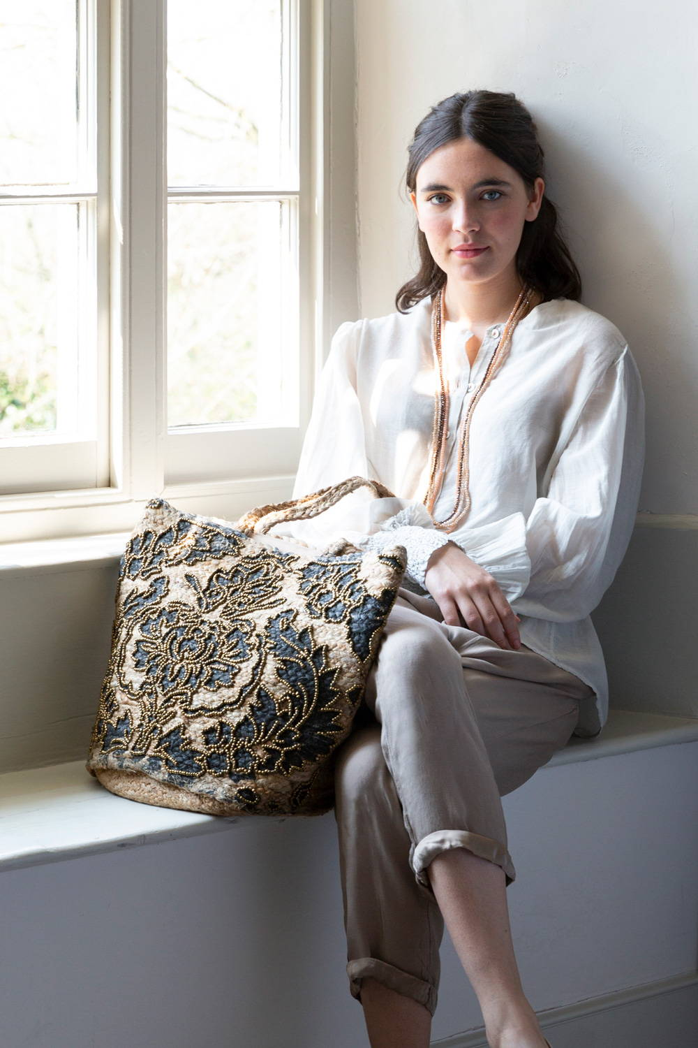 Model wearing silk blouse, crystal necklaces and a beaded straw tote bag.