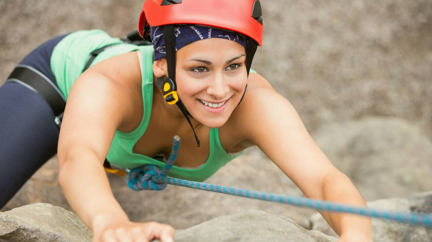 Happy girl climbing rock face wearing red helmet | Rewire Your Implicit Memory for a Happier Life | Featured | perceptual priming