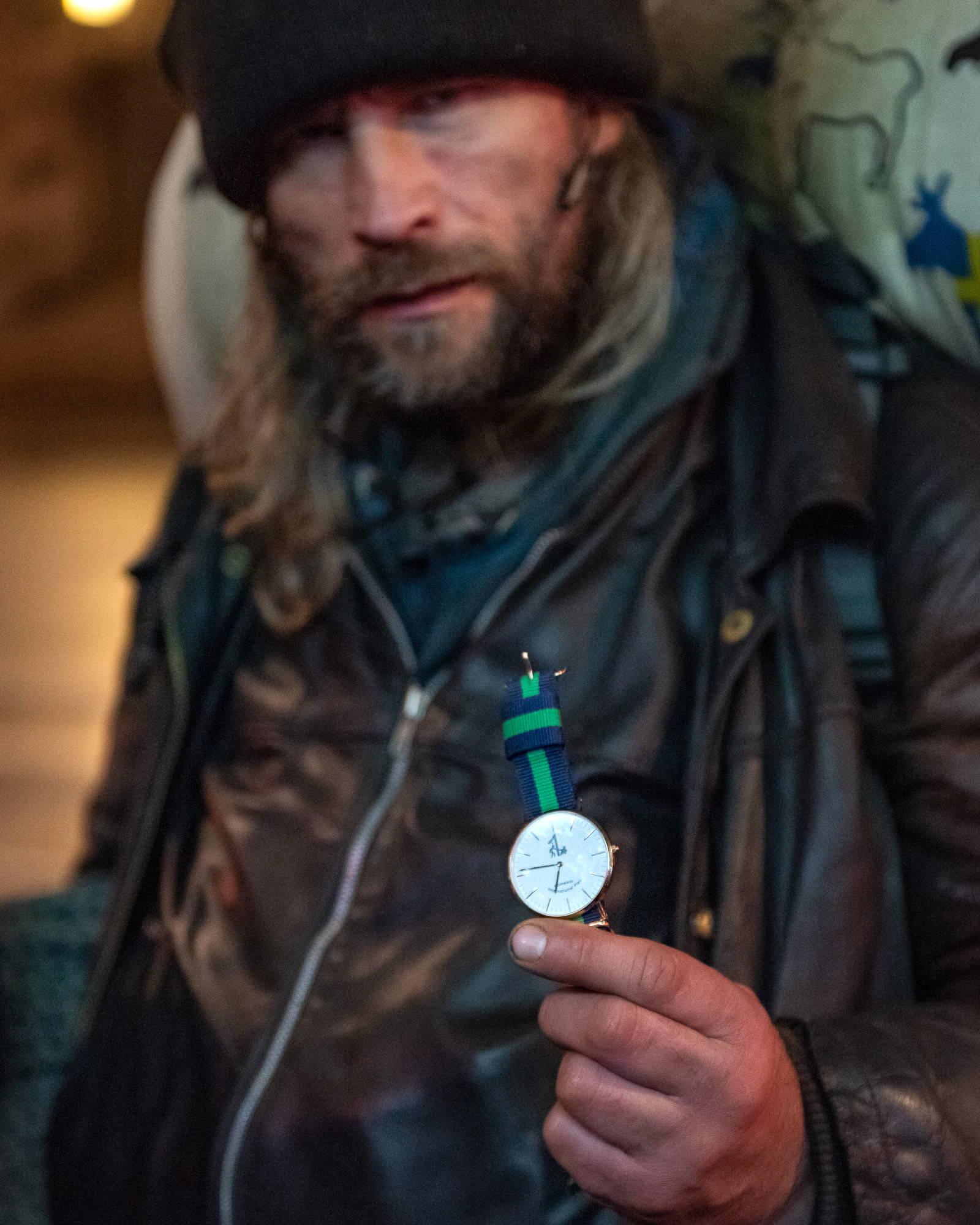 Homeless man holding wristwatch