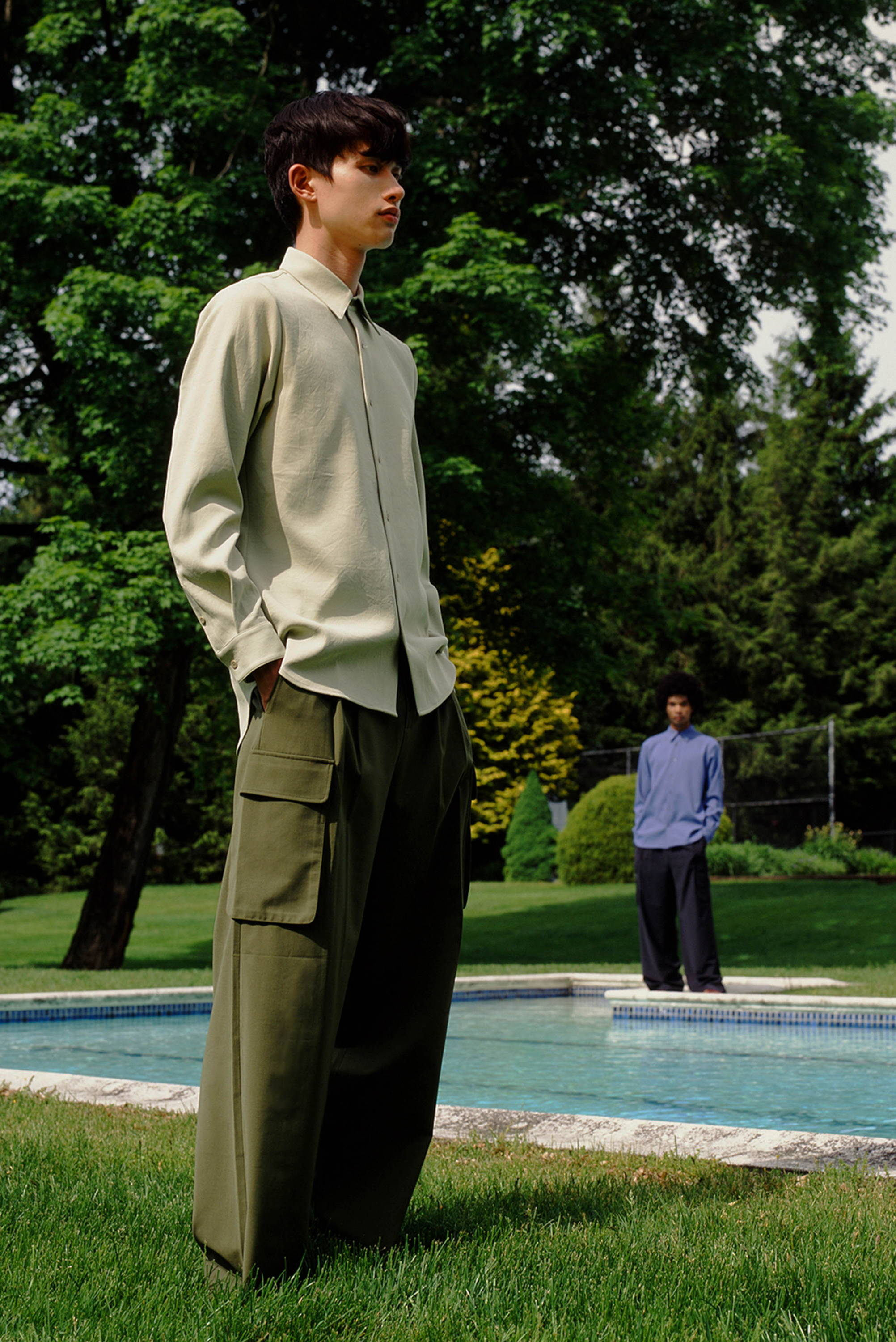 Male model standing in front of pool wearing green button down and cargo pants.
