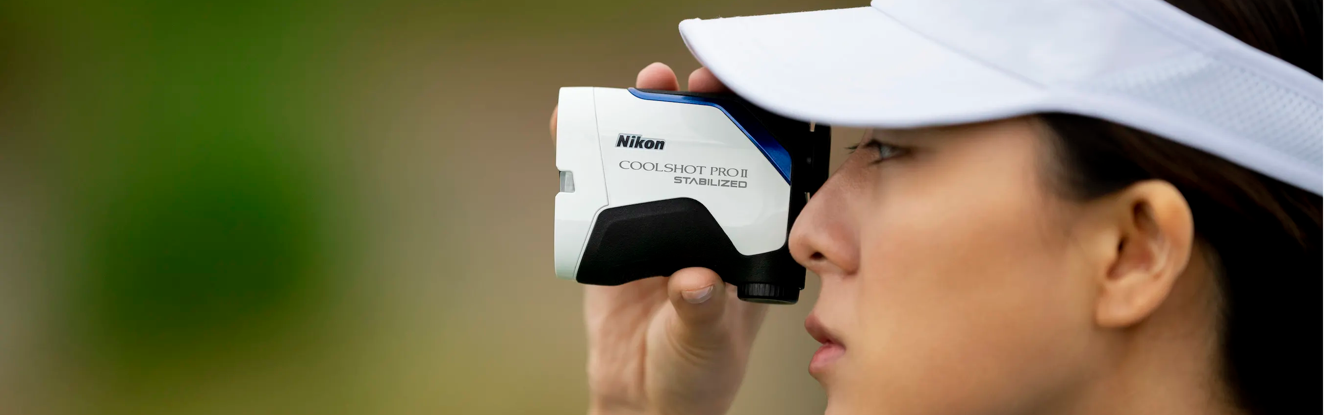 Golfer looking through a Nikon rangefinder on the course