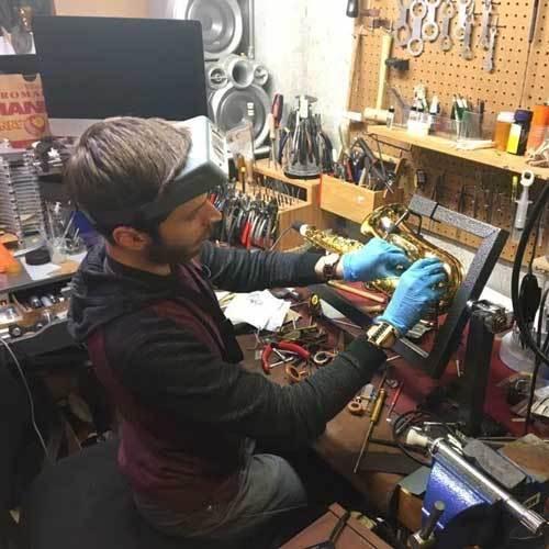 Saxophone repairman Will Peak working on an alto saxophone