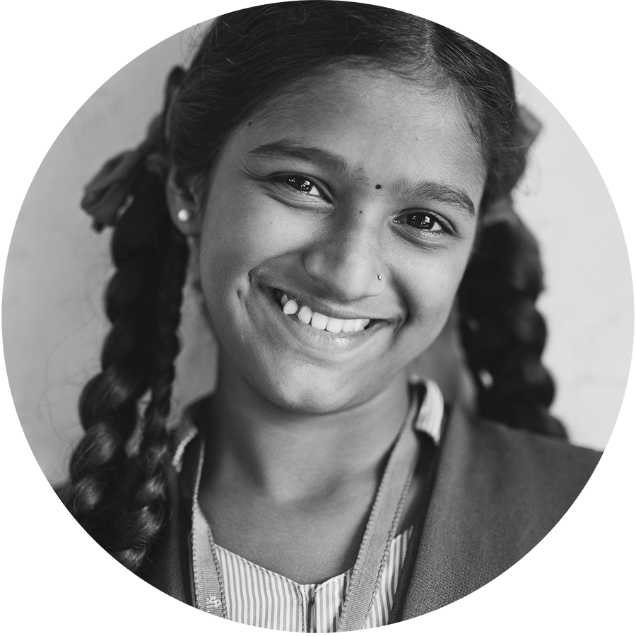 A young Indian girl with braided pigtails smiling at the camera