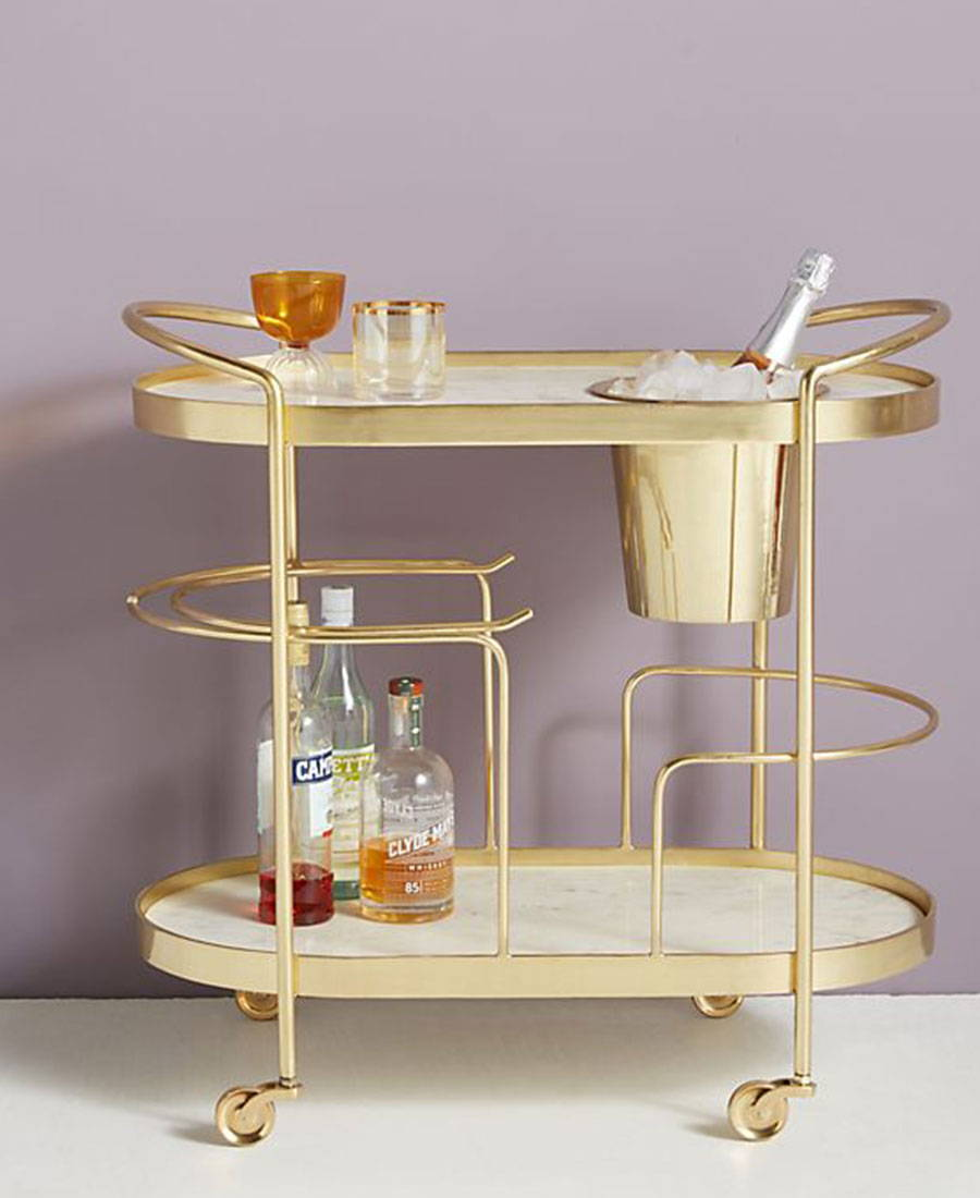 A gold bar cart with a built in ice bucket.