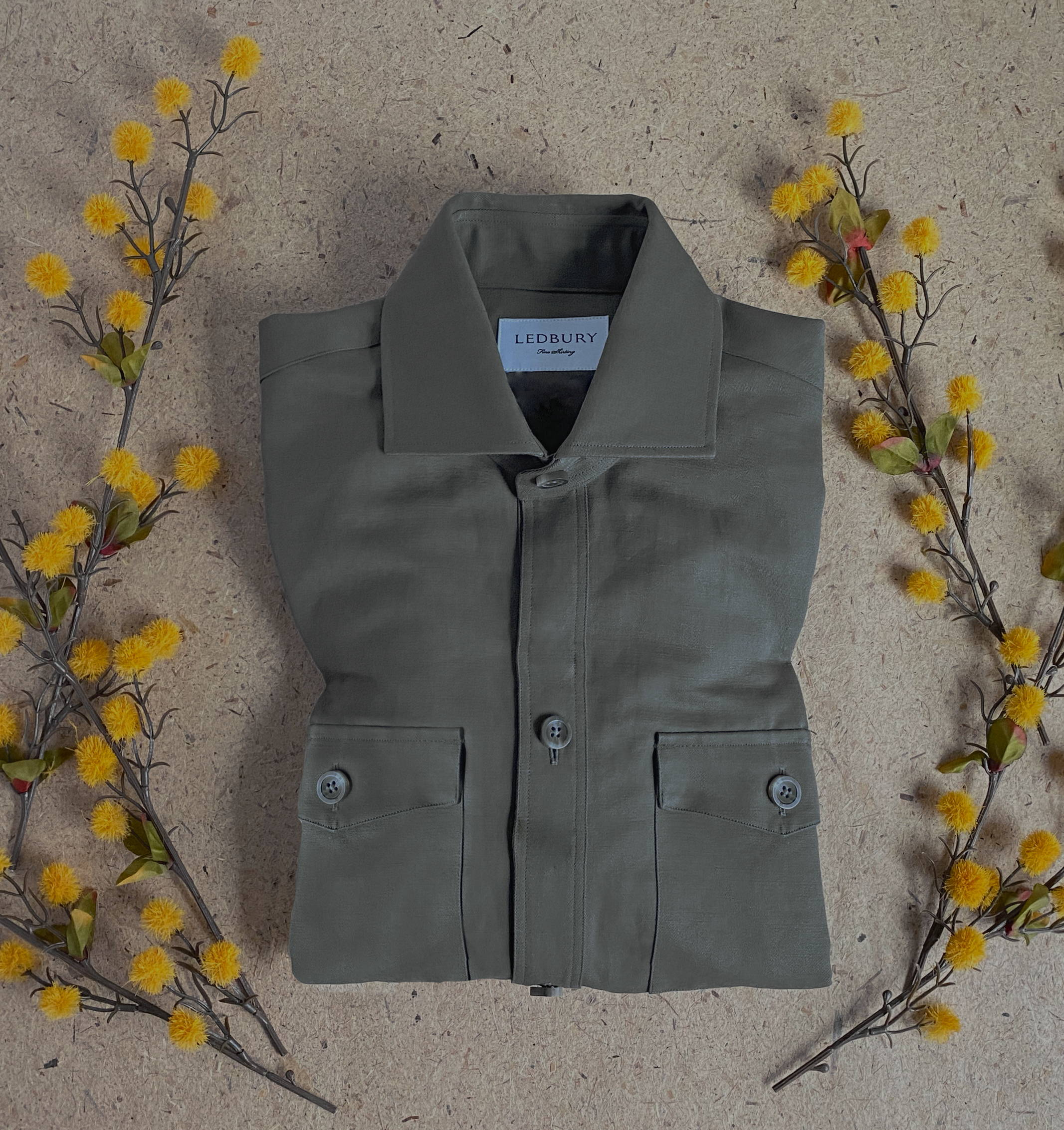 The Alexander Shirt Jacket folded and surrounded by yellow foliage