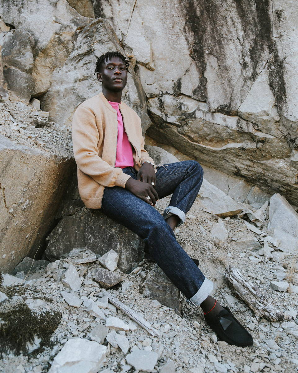 Male model sitting on a bolder with selvedge jeans and a beige knit sweater.