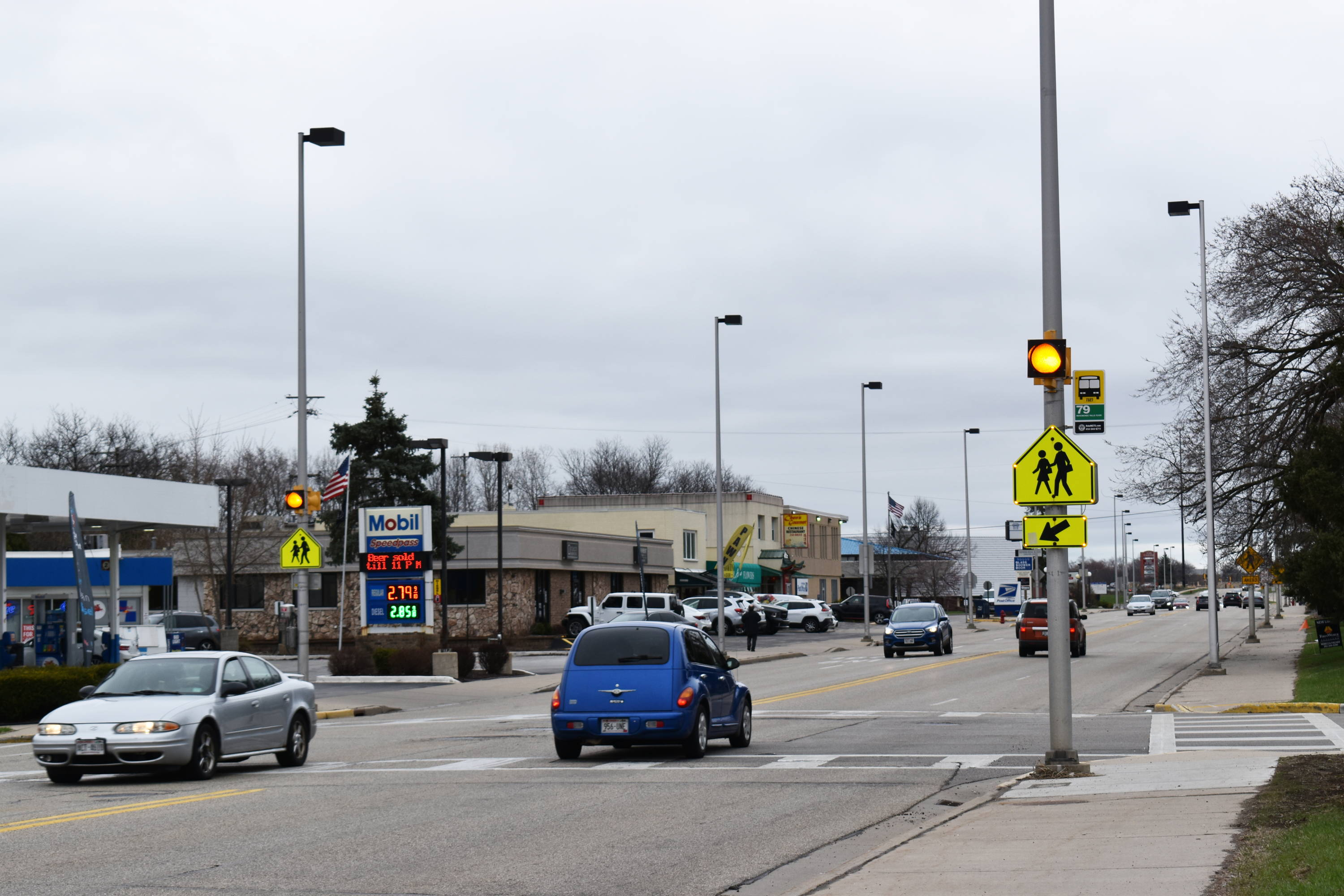 Flashing LED beacons draw awareness to pedestrian crosswalk.