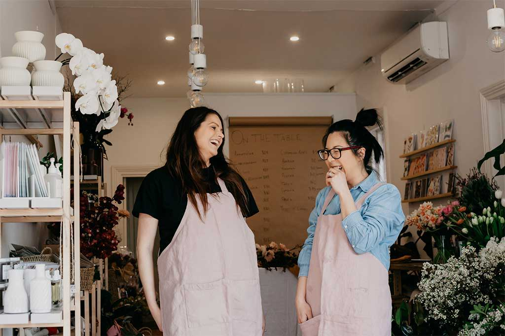 Carla and Jess of The Ivy League in CULTIVER Jude Linen Aprons.