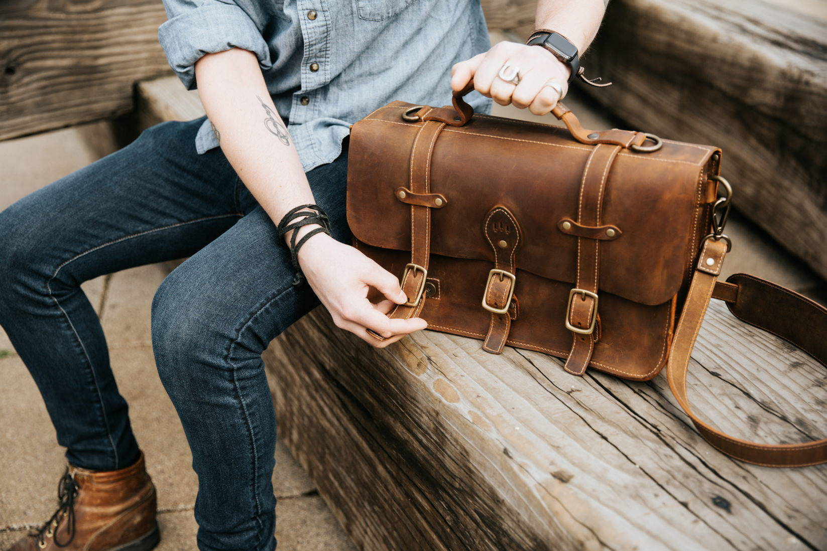 man unbuckling leather messenger bag