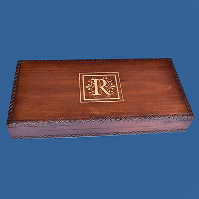 A brown wood box engraved with a initial.