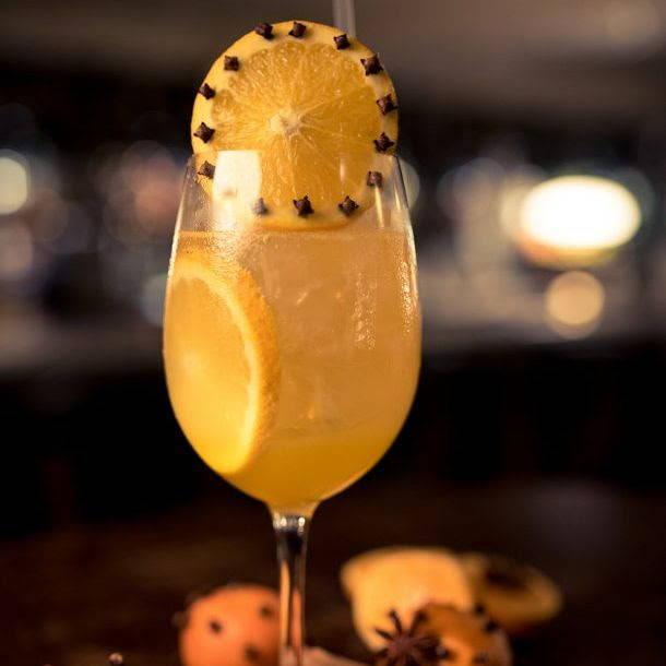 clove clementine cocktail with orange garnish in a glass