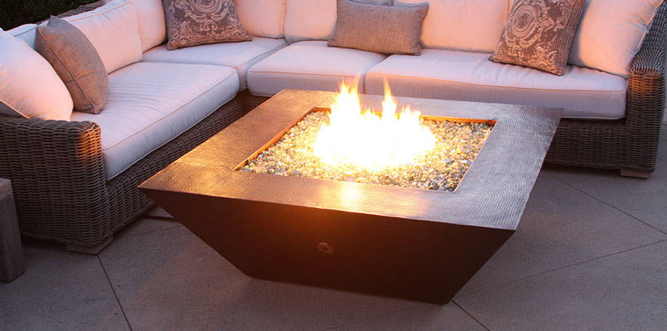 A hand hammered copper Moreno fire pit is nestled next to an outdoor sectional.