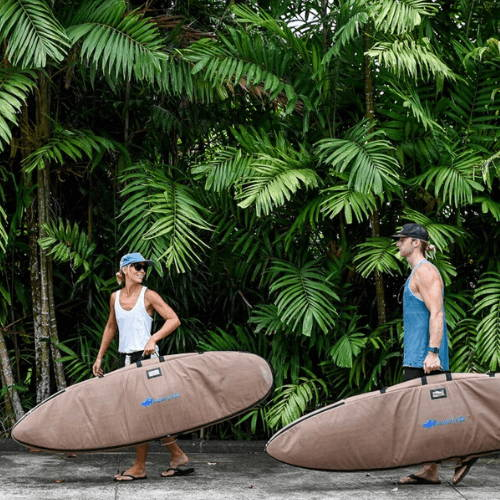 Two Surfers Carrying Wave Tribe Surfboard Travel Bags