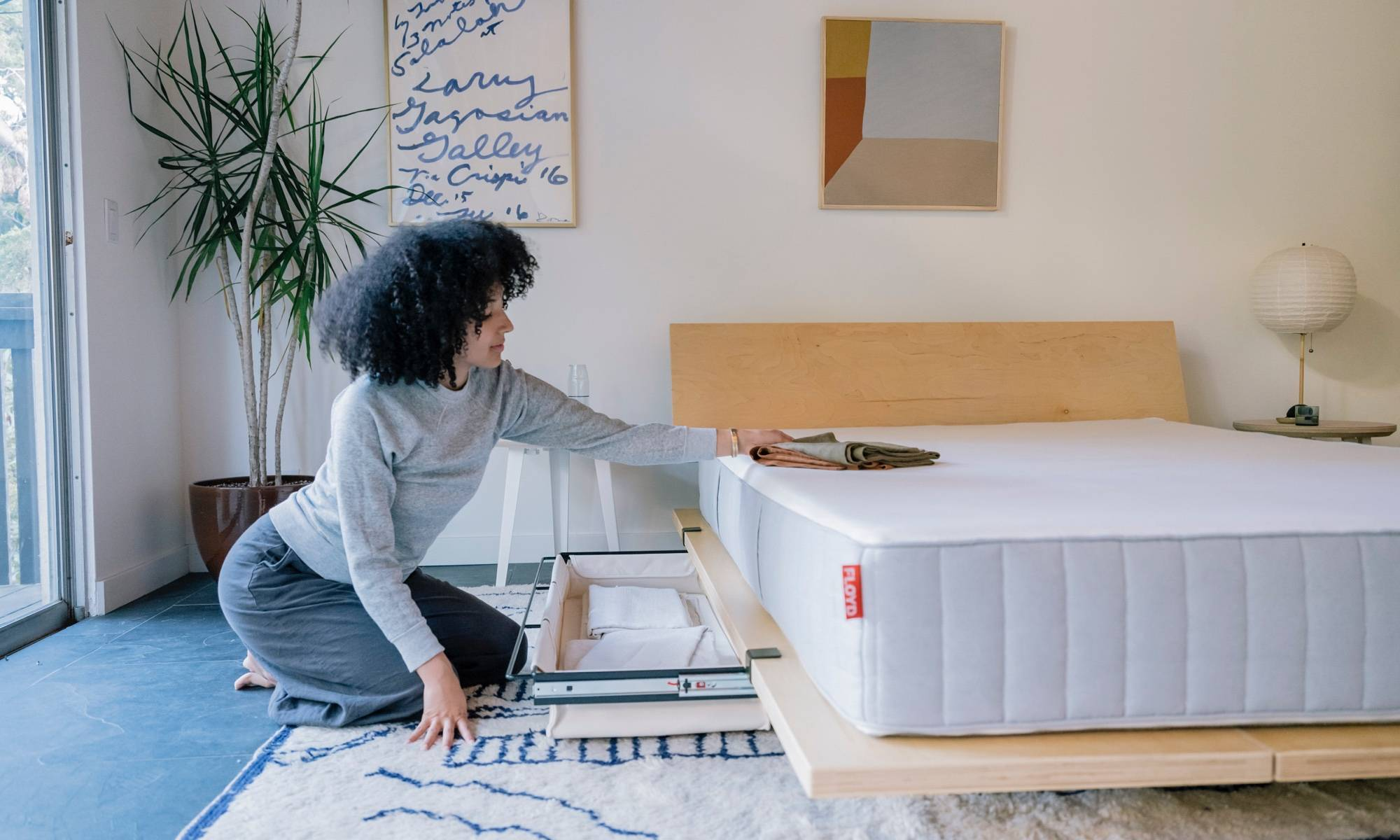 A woman putting away sheets in her Floyd underbed storage.
