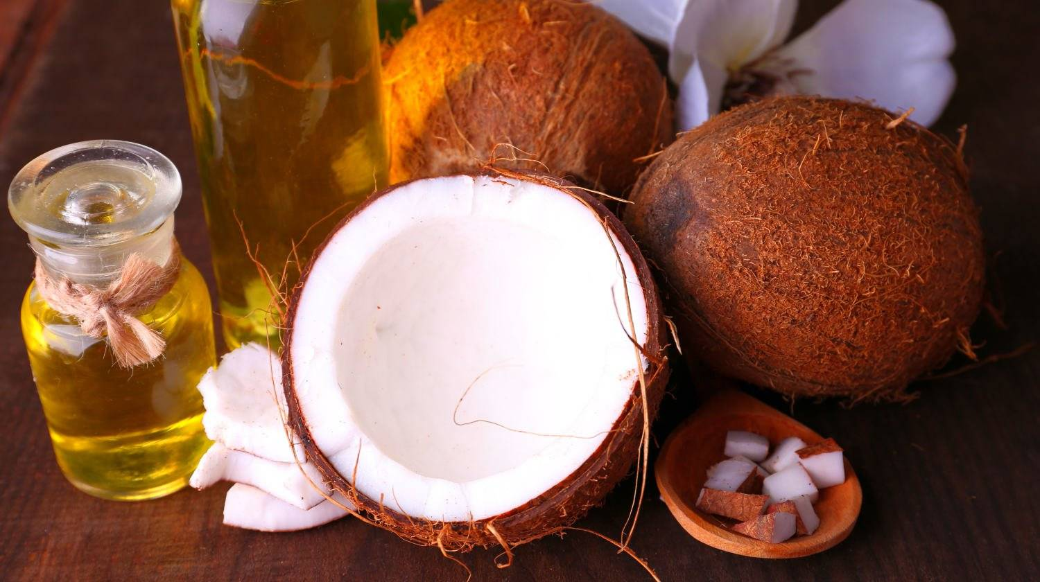 Coconuts and coconut oil on wooden table | The Best Uses For Coconut Oil For Health And Wellness | coconut oil uses | uses of coconut oil | Featured