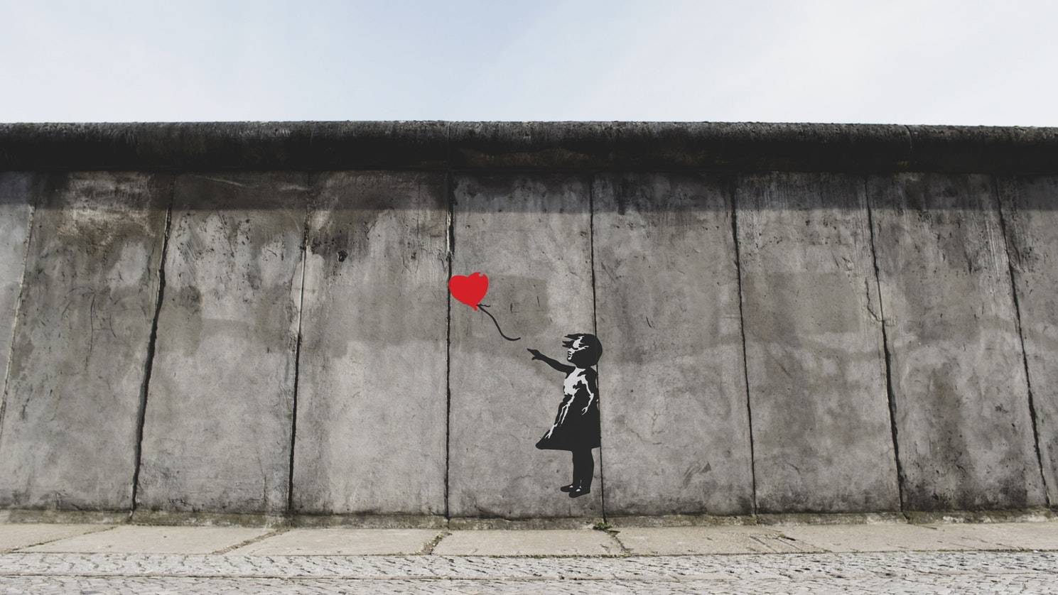 Banksy. Image of a girl with a red balloon on a concrete wall