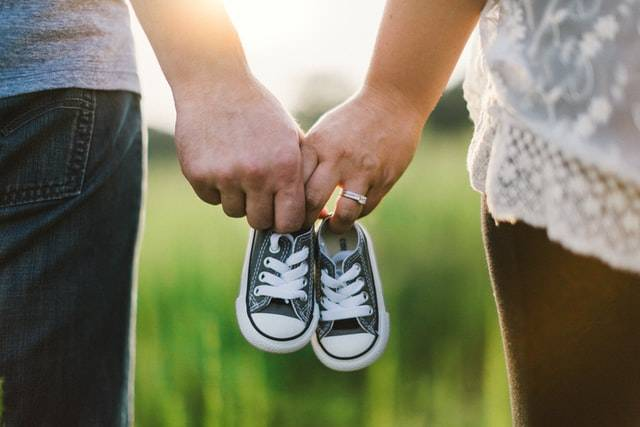 Couple Holding Kids Shoes